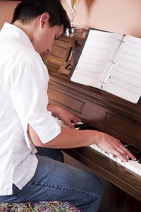 Un adolescent apprenant le piano avec la méthode Colin
